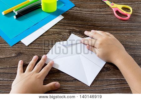 The Child Holds A Paper Strip Square And Fold It Corner. The Child Makes Crafts Out Of Paper Boat. G