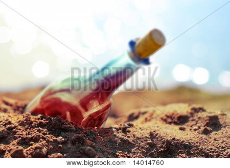 Colored bottle in sand on beach