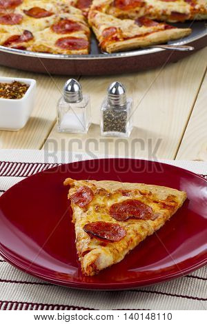 pepperoni pizza with salt and pepper shaker