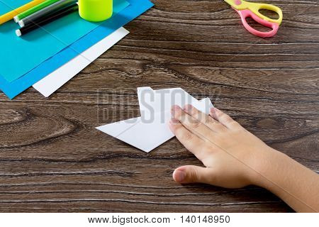 The Child Holds A Paper Strip Square And Fold Him In Half. The Child Makes Crafts Out Of Paper Boat.