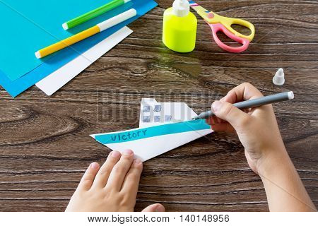 The Child Does The Victory Inscription. The Child Makes Crafts Out Of Paper Boat. Glue, Paper, Sciss
