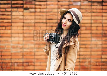 cute girl photographer on a background of a brick wall . young woman takes on a film camera on the street
