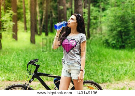 Young woman drinking water after riding an exercise bike on nature park forest