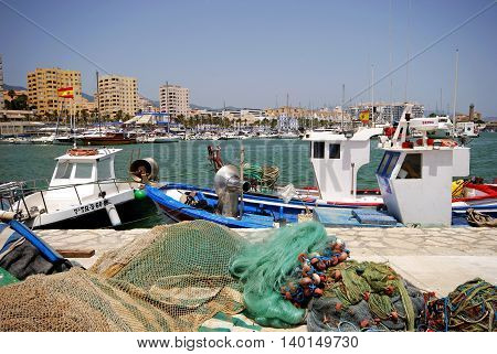 ESTEPONA, SPAIN - JULY 18, 2008 - Traditional fishing boats and nets in the harbour with yachts and the marina to the rear Estepona Malaga Province Andalusia Spain Western Europe, July 18, 2008.