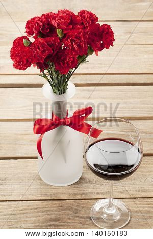 close up image of red flower and wine decorated on table