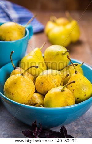 some raw ripe small yellow pears in blue dish on wooden background