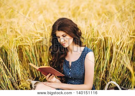 Girl in dress reading book sitting on a grass in field. Sunny morning.