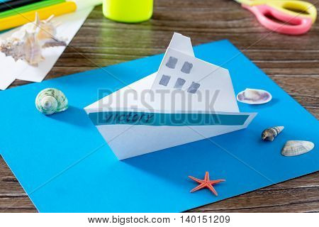 The Child Does Crafts Out Of Paper Boat. Glue, Paper, Scissors On A Wooden Table. Children's Art Pro