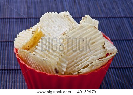 fried potato chips in red plastic bowl