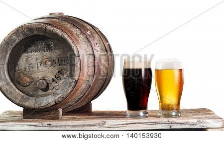 Glasses of  beer and ale barrel on the wooden table. Craft brewery. Clipping paths.