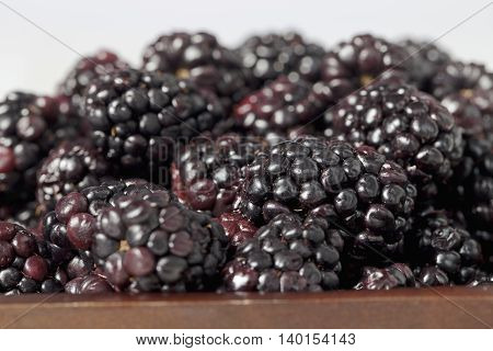 a pile of blackberries on the bowl