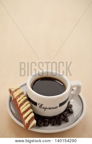 hot coffee with biscuit and coffee beans in a white saucer