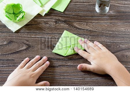 The Child Holds A Paper Square And Fold It Corner. The Child Makes Crafts Out Of Paper Lily. Paper N
