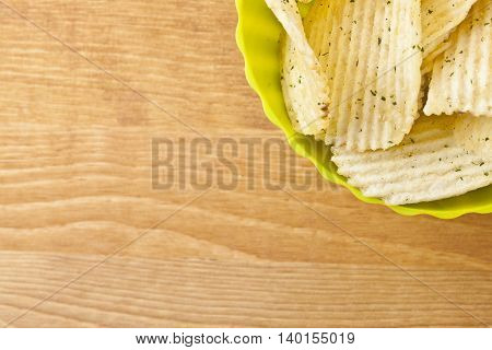 sour cream flavored potato chips in green bowl