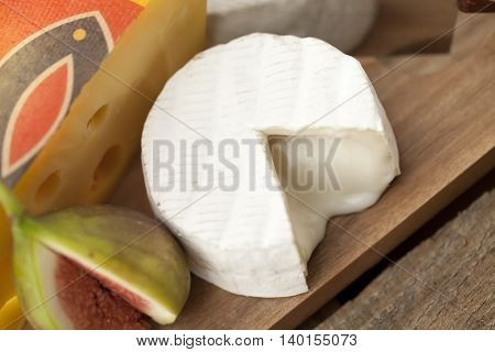 slice cheese and fig on wooden board
