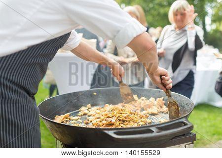 Cheff preparing traditional Slovenian kaiserschmarrn in big pan on open air garden banquet.