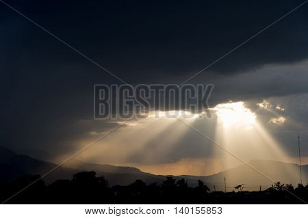 Rays of light shining through dark clouds . dramatic sky with cloud
