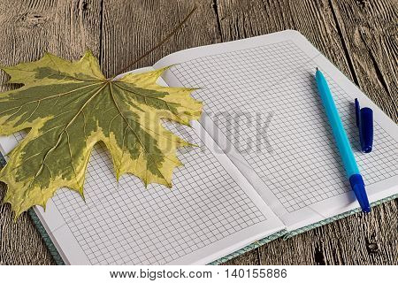 Exercise book in a cage, ball pen and maple leaf on a wooden table.
