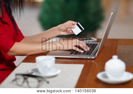 Hands holding credit card and using laptop. Female hands with a credit card and laptop closeup. Female hands making online payment. Purchase online. Buy online. Online shopping