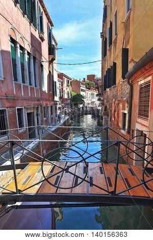 VENICE, ITALY - SEPTEMBER 9, 2010: Easy bridge on narrow canal in Venice.  Sunny Day