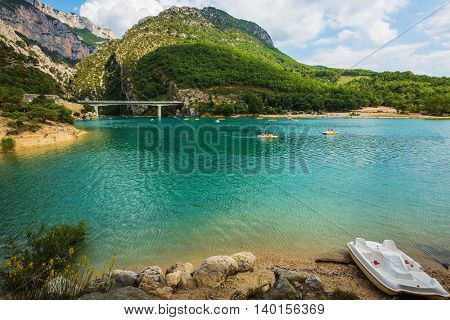 Big bridge over river Verdon in Provence.  White catamarans are sailing on turquoise water. National park Merkantur, France