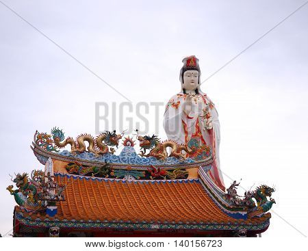Guanyin and chinese dragon statue on the  temple roof.