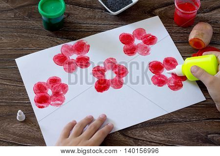 Drawing On Paper Poppies, Child Apply Glue To The Paper Poppies. Glue, Paint, Paper And Potatoes On