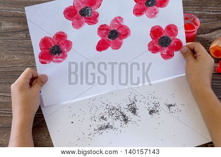 Drawing On Paper Poppies, Child Draws Poppy Seeds. Glue, Paint, Paper And Potatoes On A Wooden Table