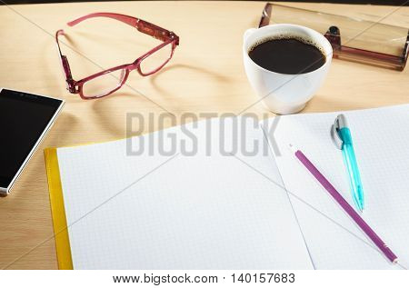 Open blank notebook with glasses, cup of coffee, mobile phone on a desk