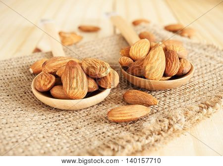 Almond in wooden spoon on wood table