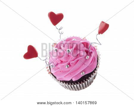 chocolate cupcake with pink icing and heart shape decoration