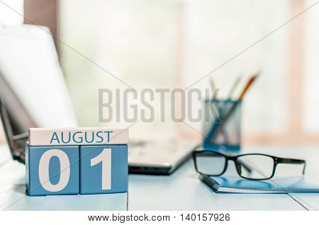 August 1st. Day of the month 1 wooden color calendar on business workplace background. Summer day. Empty space for text.