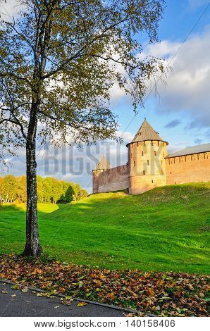 Architecture autumn city landscape - towers and walls of Veliky Novgorod Kremlin on the hill under warm sunset light framed by autumn trees in Veliky Novgorod Russia