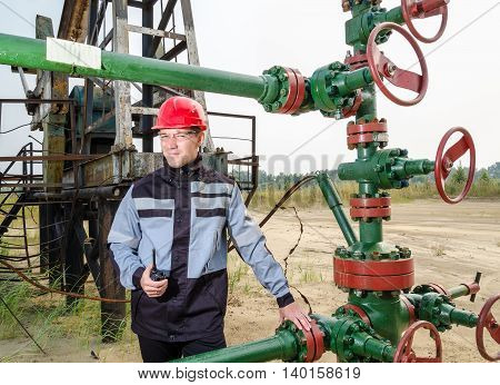 Oilfield worker near wellhead wearing red helmet and work clothes holding the radio. Oil and gas concept.