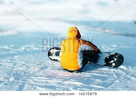 Snowboard sportsmen sitting on blue snow