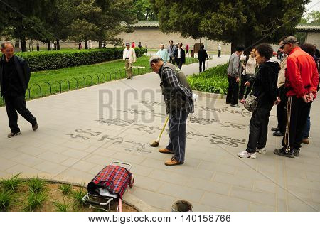 April 26, 2016 Tiantan Park, Beijing, China. A elderly Chinese man righting Chinese calligraphy with water on the walkway within Tiantan park in Beijing China as others watch.