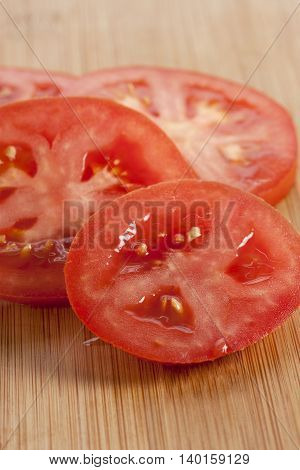 slices of fresh tomatoes on the wooden table