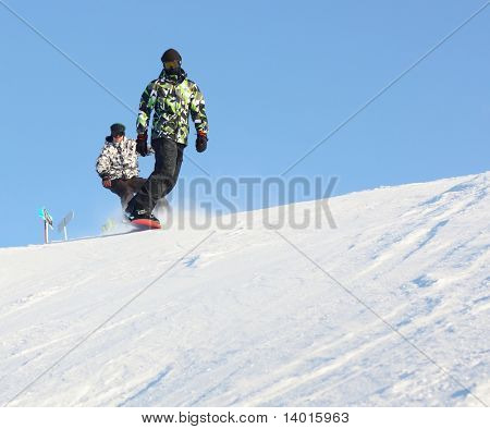 Snowboard sportsmen in motion over clear blue sky