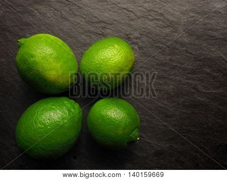 Fresh organic lime fruits on a dark slate background healthy food background with space for text