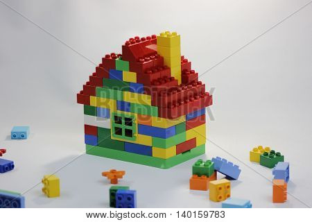 Colorful toy house with window roof and chimney. Around are colorful bricks in mess.