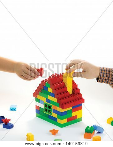 Toy house built by family - husband and wife. Their hands have rings. The symbol of building relationships