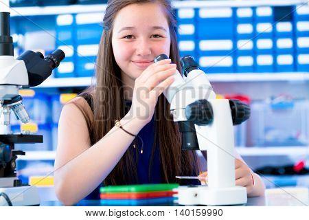 Teen girl in school laboratory. Researcher working with binocular microscope