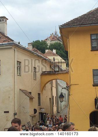 Romania, August 21, 2015, Sighisoara, Transylvania, People near an old street entrance