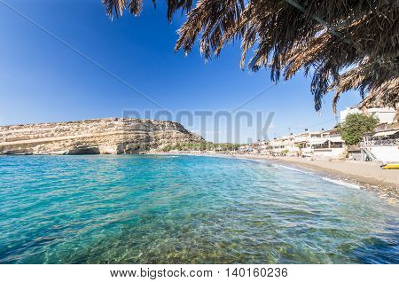 Matala beach on Crete island, Greece. Tourists relax and bath in crystal clear water of Matala in south of Creta. There are many caves near the beach.