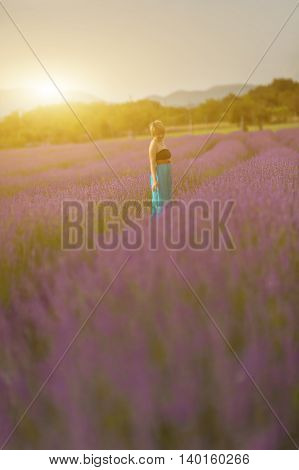 Young woman wearing blue dress posing in a lavender field. Concept positive mood. Selective focus on woman.