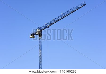Big and tall slender crane on background of blue sky