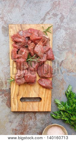 Diced raw meat  with a sprig of rosemary on chopping board. Top view, blank space