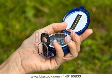 closeup of hand with compass on nature background