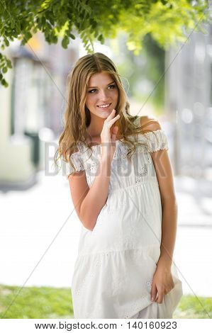 Pregnant woman in a white summer dress