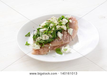 preparing filled chicken breast fillet the raw poultry meat with filling of feta cheese and arugula salad on a white plate white wooden background selected focus